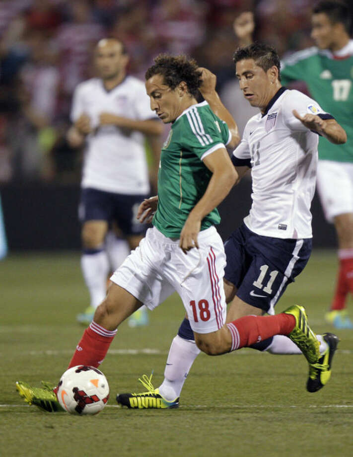 Mexico's Andres Guardado, left, kicks the ball away from United States' Alejandro Bedoya during the first half of a World Cup qualifying soccer match Tuesday, Sept. 10, 2013, in Columbus, Ohio. (AP Photo/Jay LaPrete)