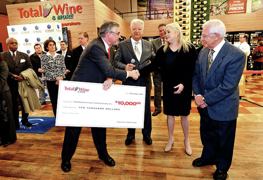Total Wine co owner David Trone, Norwalk Mayor Richard Moccia thank Food Bank Executive Director Kate Lombardo and Food Bank Board Chair Sam Cingari while Total Wine presents a check to the Food Bank of Lower Fairfield County for $10,000 during the wine stores grand opening on Main Ave in Norwalk Thursday afternoon. / ©2012 The Hour Newspapers