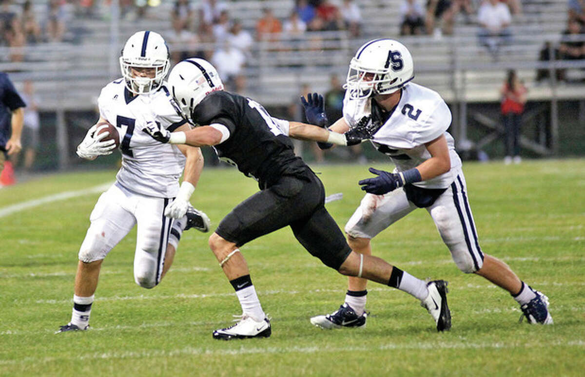 Hour Photo/Danielle Calloway Staples' Owen Burke, left, looks for running as a Xavier player looks to ward off the block of the Wrckers' Will Johnson, right, during the season's kickoff game against Xavier at Palmer Field in Middletown on Wednesday.