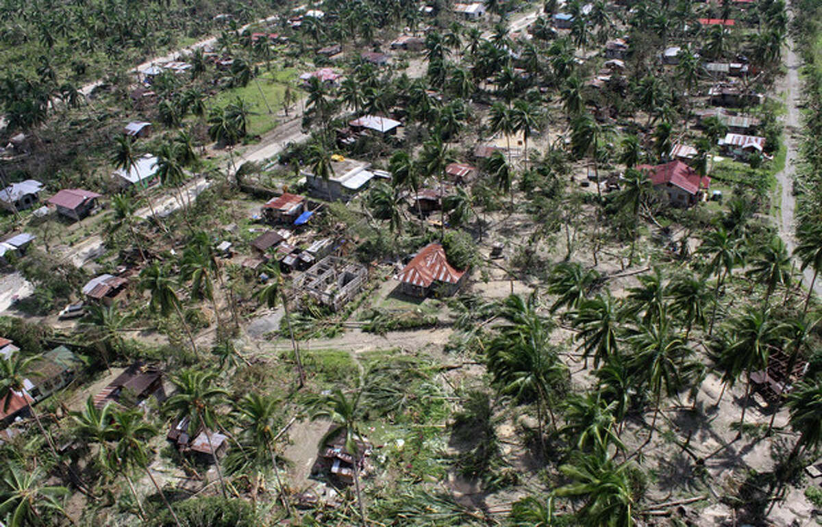 This photo released by the Philippine Army's 10th Infantry Division shows an aerial view of houses damaged by flash floods caused by Typhoon Bopha in Compostela Valley province, in the southern Philippines on Thursday Dec. 6, 2012. The powerful typhoon that washed away emergency shelters, a military camp and possibly entire families in the southern Philippines has killed hundreds of people with nearly 400 missing, authorities said Thursday. (AP Photo/Philippine Army 10th Infantry Division) NO SALES