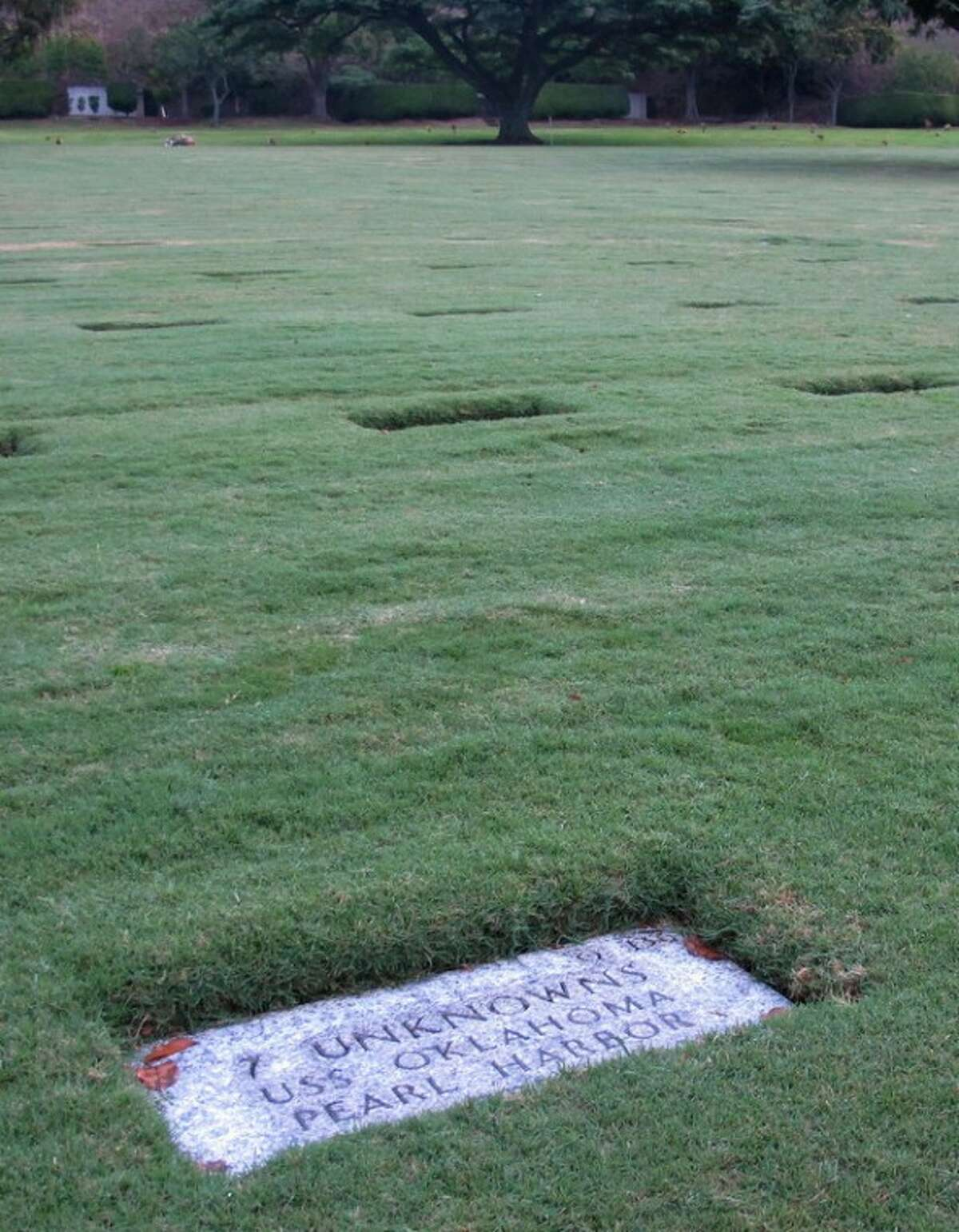 This Dec. 5, 2012 photo at the National Memorial Cemetery of the Pacific in Honolulu shows a gravestone identifying it as the resting place of 7 unknowns from the USS Oklahoma who died in Japanese bombing of Pearl Harbor. The Navy and National Park Service will honor Ray Emory, a Pearl Harbor survivor who pushed to put ship names on the gravestones and identify unknown remains, on Dec. 7 for his determination to have Pearl Harbor remembered, and remembered accurately. (AP Photo/Audrey McAvoy)