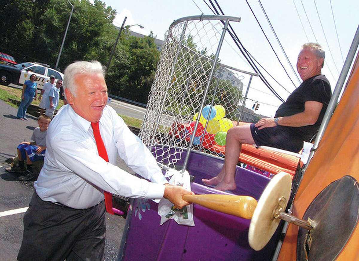 Hour file photo / Alex von Kleydorff Above, Mayor Richard Moccia brought his own baseball bat to hit the target and dunk then-Police Chief Harry Rilling at Tip-A-Cop at Ash Creek Saloon in this July 22, 2010, file photo. Below left, Moccia holds a press conference with Rilling at City Hall to comment on gang-related arrests and murder investigations in this Aug. 19, 2010, file photo. Below right, Moccia and Rilling read to third-graders at Brookside School for Read Across America Day in this March 5, 2011, file photo.