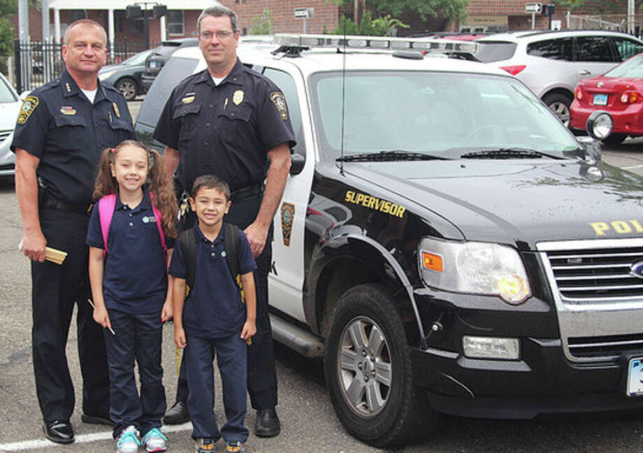Hour photo / Chris BosakIsabella and Cristian Cuartas stand in the Side by Side Charter School parking lot with Norwalk Police Chief Thomas Kulhawik and Deputy Chief David Wrinn. The children's parents won an auction whereby the prize was a ride to school for the parents by the police.