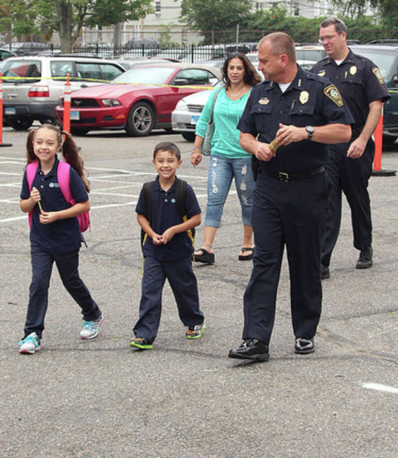 Hour photo / Chris BosakIsabella and Cristian Cuartas walk into Side by Side Charter School with Norwalk Police Chief Thomas Kulhawik and Deputy Chief David Wrinn. The children's parents won an auction whereby the prize was a ride to school for the parents by the police.