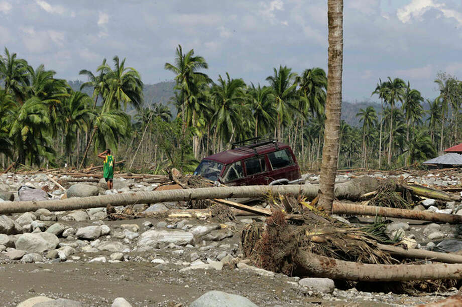 A resident searches for victims of Tuesday's devastating storm in New Bataan township, Compostela Valley in the southern Philippines Thursday, Dec. 6, 2012. The powerful typhoon that washed away emergency shelters, a military camp and possibly entire families in the southern Philippines has killed hundreds of people with nearly 400 missing, authorities said Thursday. (AP Photo/Bullit Marquez) / AP