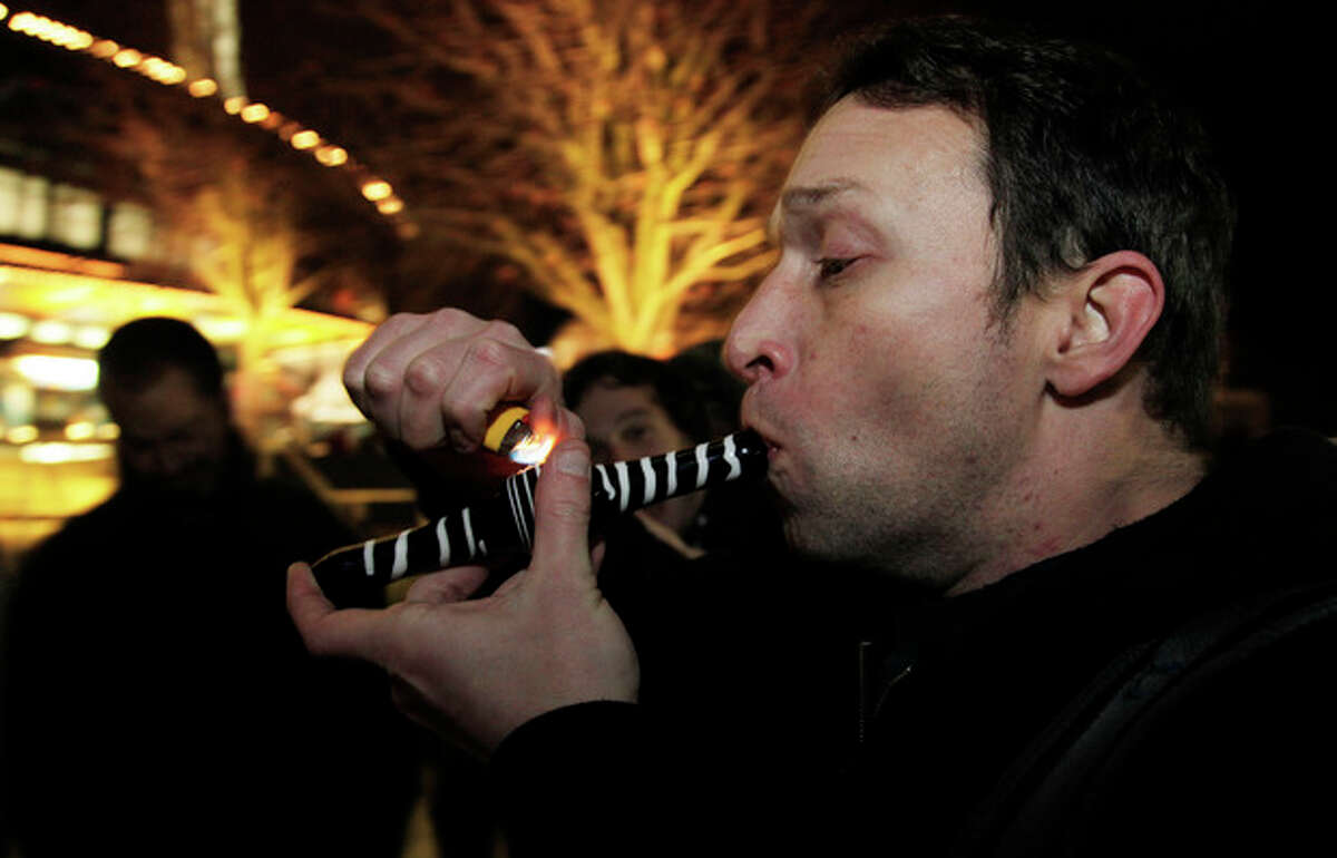 Gary Parrish smokes marijuana in a glass pipe, Thursday, Dec. 6, 2012, just after midnight at the Space Needle in Seattle. Possession of marijuana became legal in Washington state at midnight, and several hundred people gathered at the Space Needle to smoke and celebrate the occasion, even though the new law does prohibit public use of marijuana. (AP Photo/Ted S. Warren)