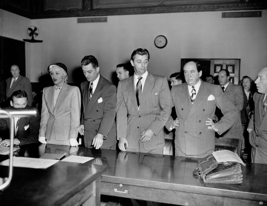 "FILE - In this Feb. 9, 1949 file photo, actor Robert Mitchum, center right, and actress Lila Leeds, left, are sentenced to 60 days in jail on charges of conspiracy to possess marijuana cigarettes in Los Angeles. On the occasion of ""Legalization Day,"" Thursday, Dec. 6, 2012, when Washington's new law takes effect, AP takes a look back at the cultural and legal status of the ""evil weed"" in American history. (AP Photo, File) / AP"