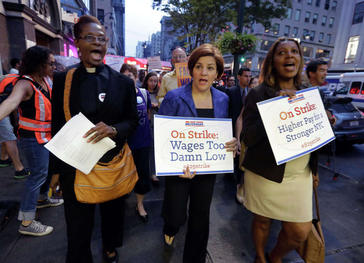 New York City Council Speaker and mayoral candidate Christine Quinn, center, accompanied by Minister Patricia Malcolm, left, and New York City Council member and public advocate candidate Letitia James, lead a fast food workers' protest march on New York's Fifth Avenue, Thursday, Aug. 29, 2013. Organizers say thousands of fast-food workers are set to stage walkouts in dozens of cities around the country Thursday, part of a push to get chains such as McDonald's, Taco Bell and Wendy's to pay workers higher wages. (AP Photo/Richard Drew)