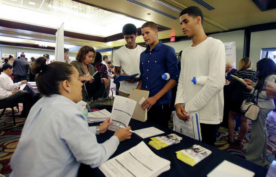 In this Wednesday, Aug., 14, 2013, photo, job seekers Emilio Ferrer, Brian ferrer, center, and Jonathan, right, of Hollywood, Fla., talk to a FirstService representative at a job fair in Miami Lakes, Fla. The Labor Department reports on the number of Americans who applied for unemployment benefits for third week of August on Thursday, Aug. 29, 2013. (AP Photo/Alan Diaz) / AP