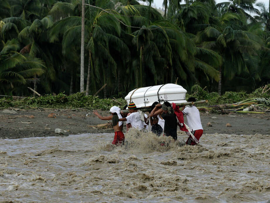 Relatives cross a river to bury their loved one, who died in a flash flood caused by Typhoon Bopha, Thursday, Dec. 6, 2012, in New Bataan township, Compostela Valley in southern Philippines. The powerful typhoon that washed away emergency shelters, a military camp and possibly entire families in the southern Philippines has killed hundreds of people with nearly 400 missing, authorities said Thursday. (AP Photo/Bullit Marquez) / AP