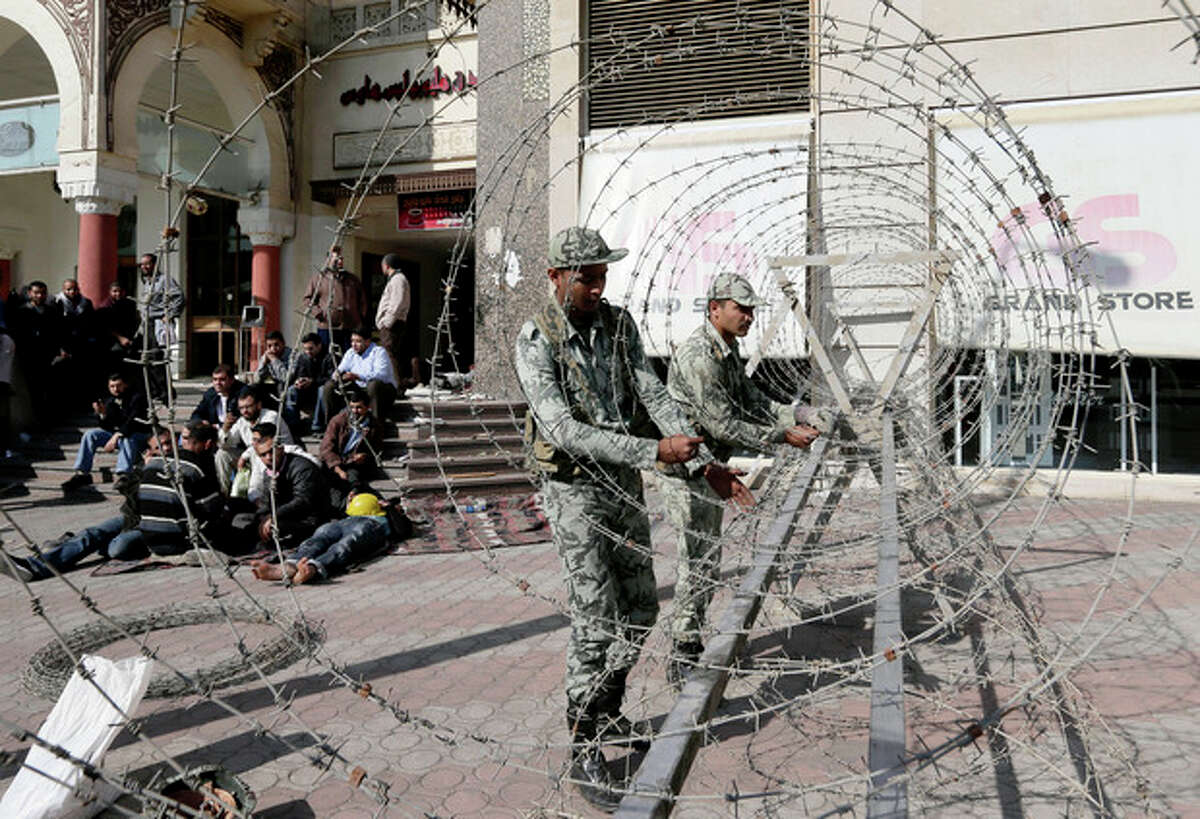 AP Photo/Hassan Ammar Supporters of Egyptian president Mohammed Morsi, left, sit as Egyptian Army soldiers lay barbed wire near the presidential palace to secure the site of overnight clashes between supporters and opponents of President Mohammed Morsi in Cairo, Egypt, Thursday, Dec. 6.