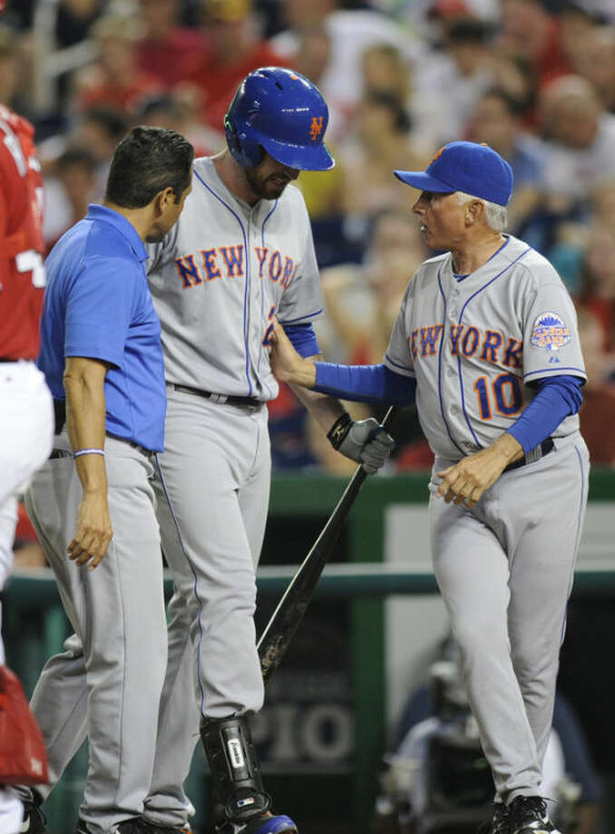 New York Mets' Ike Davis, center, is tended to by a trainer and manager Terry Collins (10) as he leaves the game after being injured batting during the third inning of a baseball game against the Washington Nationals, Saturday, Aug. 31, 2013, in Washington. (AP Photo/Nick Wass)