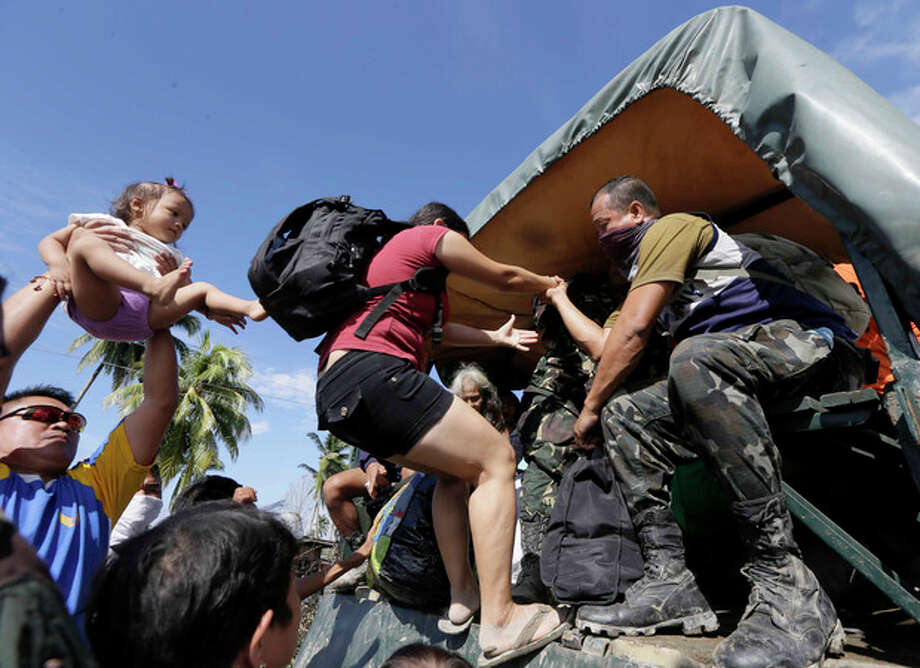 Residents are evacuated to safer grounds Thursday, Dec. 6, 2012 at New Bataan township, Compostela Valley, after Typhoon Bopha hit southern Philippines. The powerful typhoon that washed away emergency shelters, a military camp and possibly entire families in the southern Philippines has killed hundreds of people with nearly 400 missing, authorities said Thursday. (AP Photo/Bullit Marquez) / AP