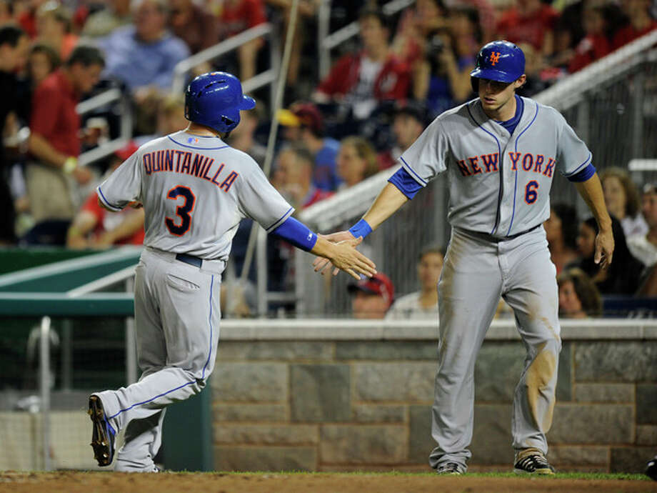 New York Mets' Omar Quintanilla (3) and Matt den Dekker (6) celebrate after they scored on a single by Eric Young Jr. during the third inning of a baseball game against the Washington Nationals, Saturday, Aug. 31, 2013, in Washington. (AP Photo/Nick Wass) / FR67404 AP