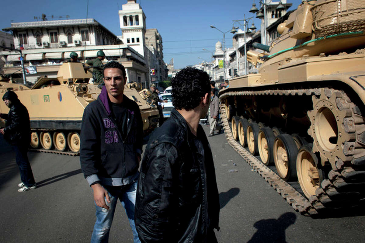 Egyptian Army tanks deploy near the presidential palace to secure the site of overnight clashes between supporters and opponents of President Mohammed Morsi in Cairo, Egypt, Thursday, Dec. 6, 2012. The Egyptian army has deployed tanks outside the presidential palace in Cairo following clashes between supporters and opponents of Mohammed Morsi that left several people dead and hundreds wounded. (AP Photo/Nasser Nasser)