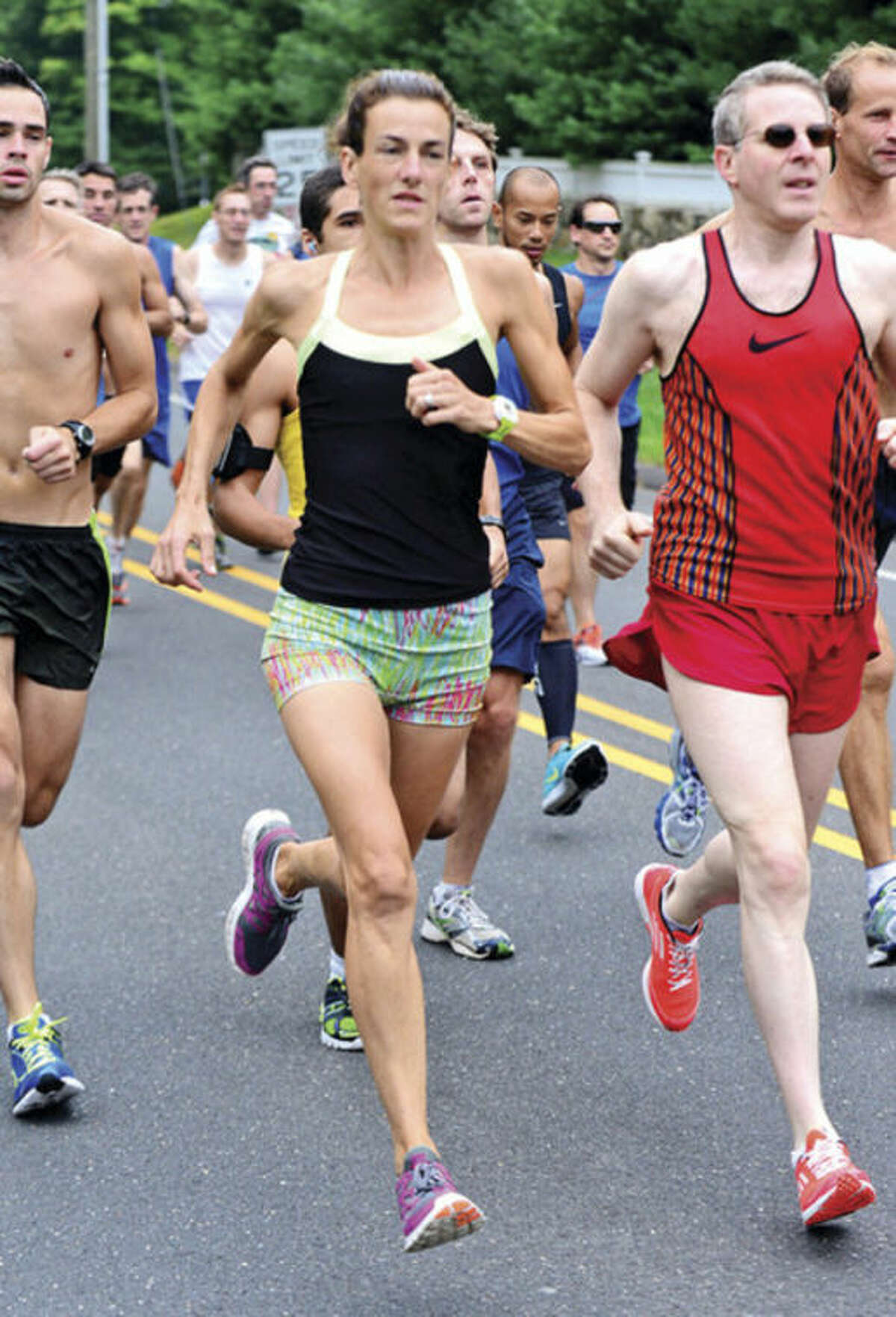 Hour photo/Erik Trautmann Mary Dolan Zengo, center, runs with the pack in the early stages of Saturday's 51st annual Labor Day Weekend 10-mile road race in Westport. She finished first among women and fourth overall.
