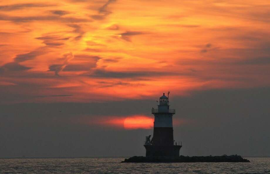 Photo by Chris Bosak The sun sets Tuesday evening as Green's Ledge Lighthouse off the coast of Norwalk stands proudly in Long Island Sound.