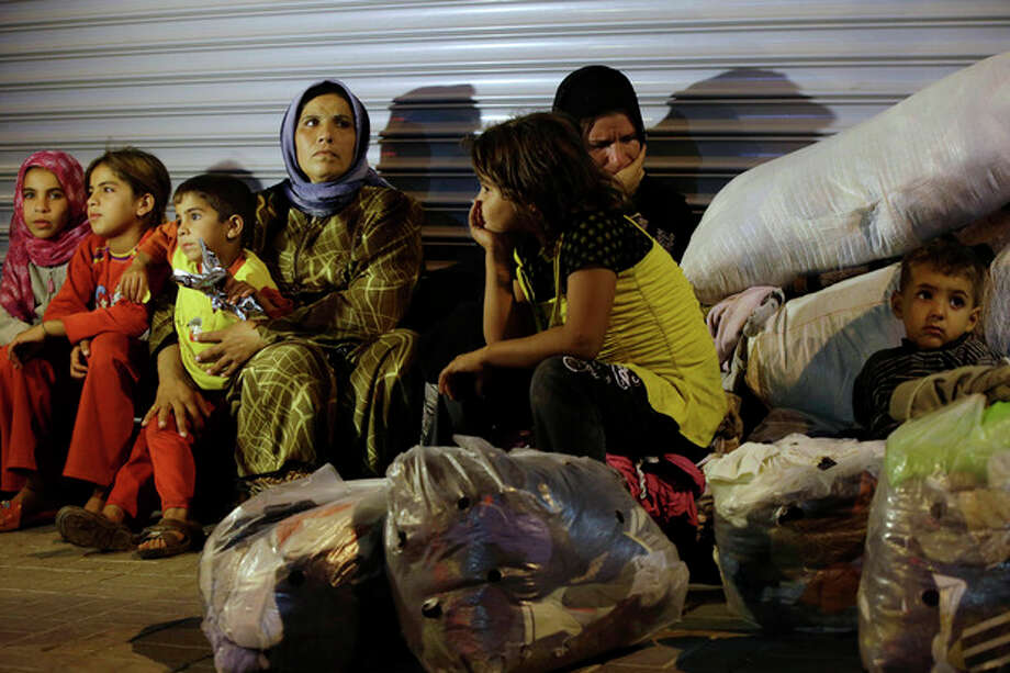 Syrian refugees stand sit in front of a closed shop in Reyhanli, Turkey, Saturday, Aug. 31, 2013. U.S. President Barack Obama said he has decided that the United States should take military action against Syria in response to a deadly chemical weapons attack, but he said he will seek congressional authorization for the use of force. (AP Photo/Gregorio Borgia) / AP