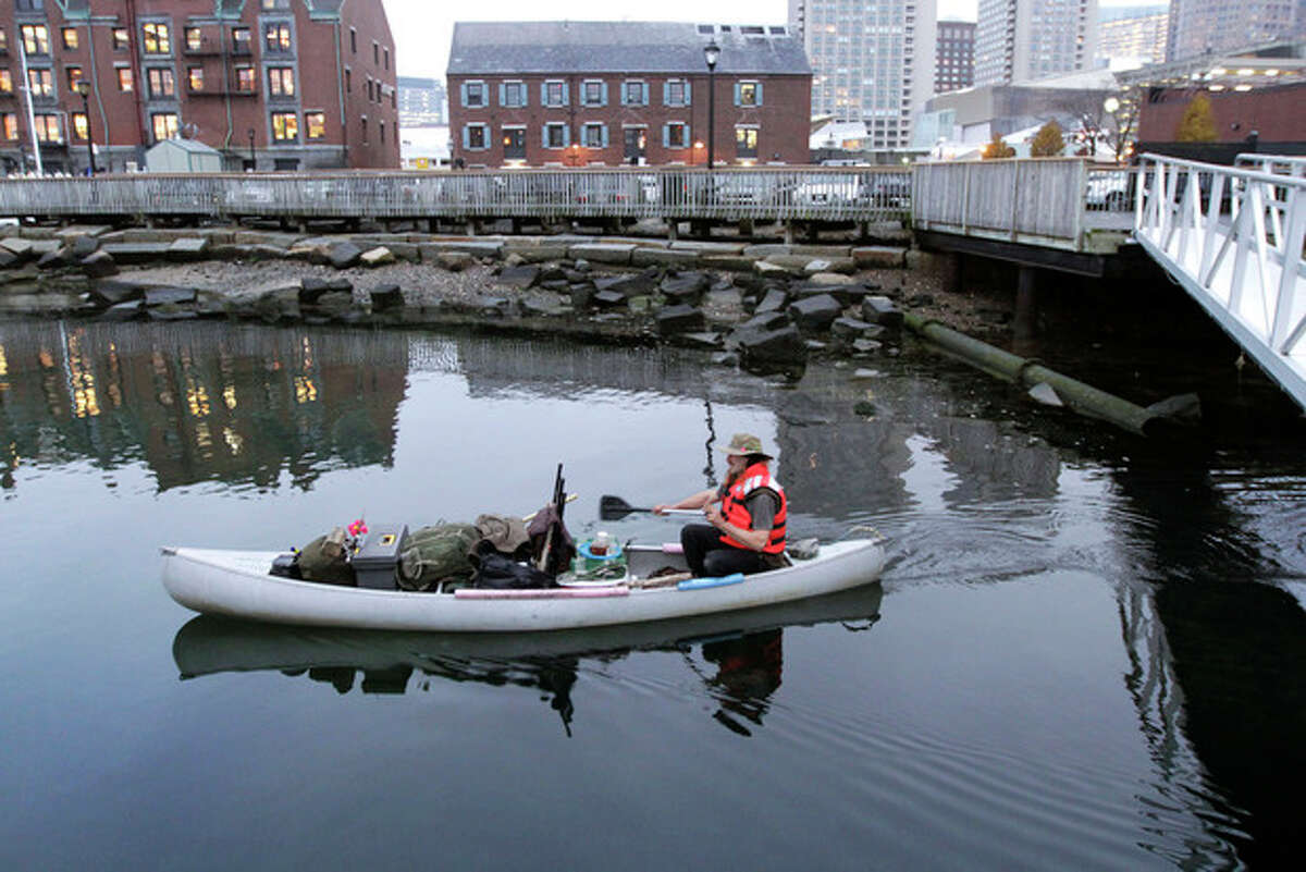 Michael Richard Smith pilots his canoe in Boston Harbor, in Boston, Tuesday, Dec. 4, 2012. The 49-year-old Maine native said Tuesday that he?'s been paddling the waters of metro Boston since at least late summer with all of his possessions aboard a 14-foot, 40-year-old aluminum canoe that he patches with duct tape when necessary. (AP Photo/Steven Senne)