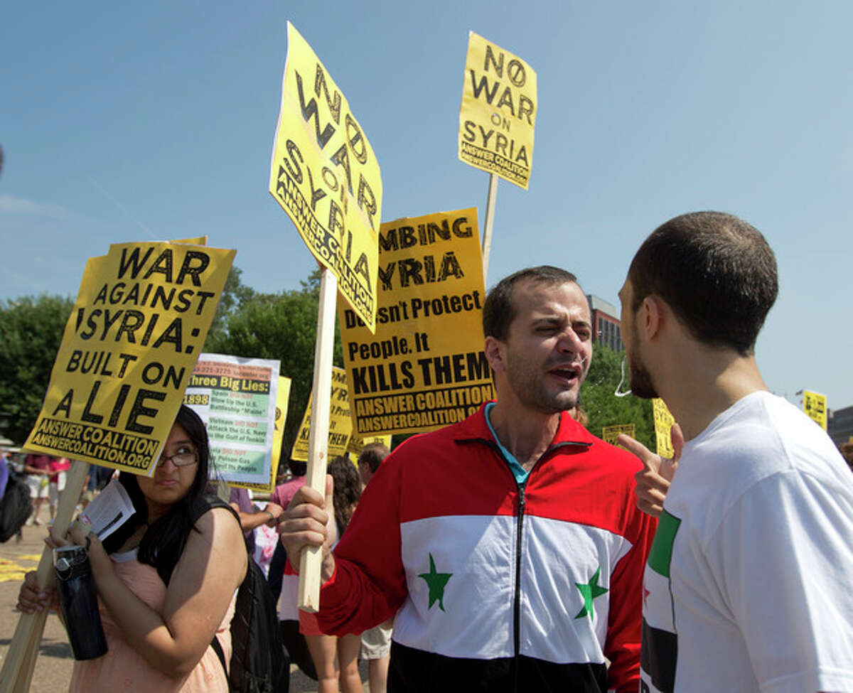 A protester in favor of U.S. military action against Syria, right, spits in the face of the man before him, who said he was from Syria, is opposed to U.S. military action there, and preferred not to give his name, during a multiple heated protests in front of the White House in Washington Saturday, Aug. 31, 2013. The man at right was arrested for spitting in the other protester's face shortly after this photo was taken. (AP Photo/Carolyn Kaster)