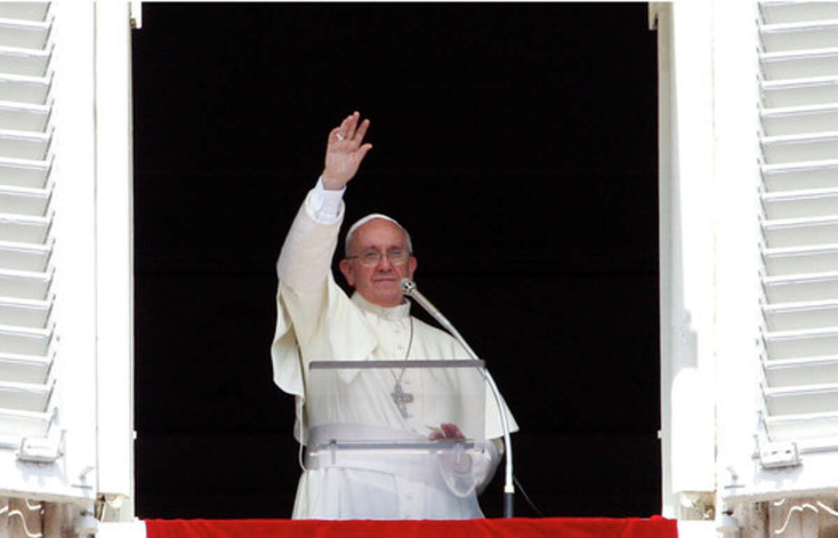 Pope Francis waves to faithful after reciting the Angelus prayer from his studio window overlooking St.Peter's Square at the Vatican, Sunday, Sept. 1, 2013. Francis is asking people to join him next weekend in a day of fasting for peace in Syria. The pontiff invited people of all faiths to join him Saturday evening in St. Peter's Square to invoke the