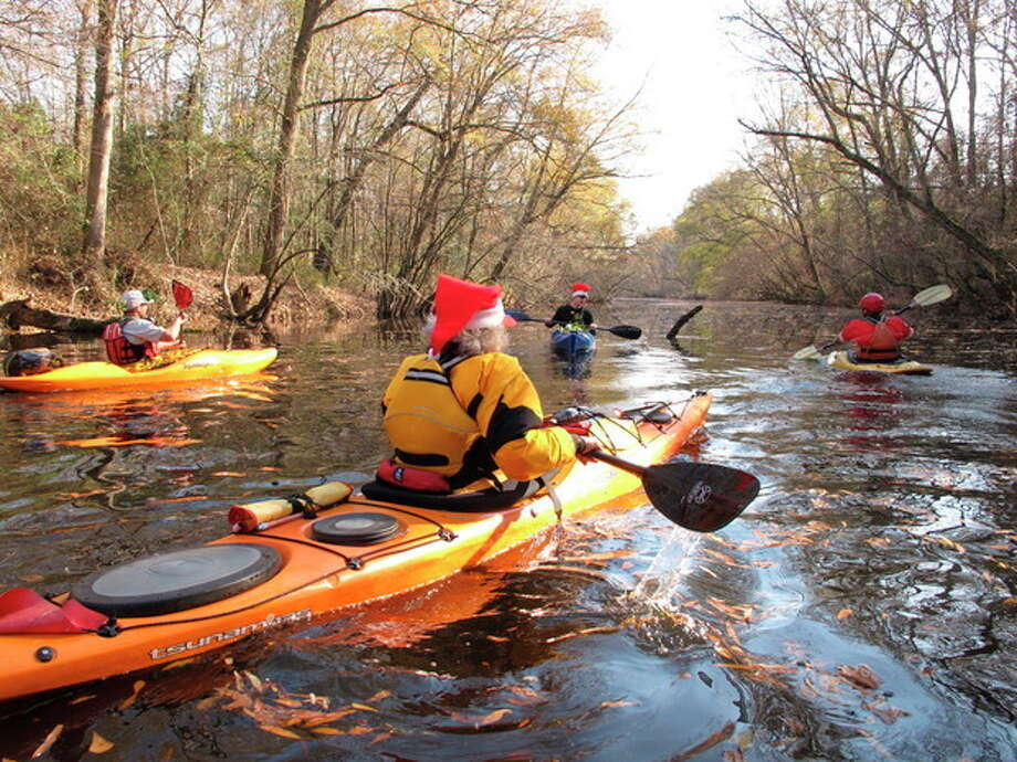 Kayakers and canoers paddle home after gathering mistletoe along the Upper Little River near Lillington, N.C., on Saturday, Dec. 1, 2012. They were part of the 30th annual Sprig Outing, which started as a fundraiser for local conservationists. AP Photo/Allen Breed) / AP
