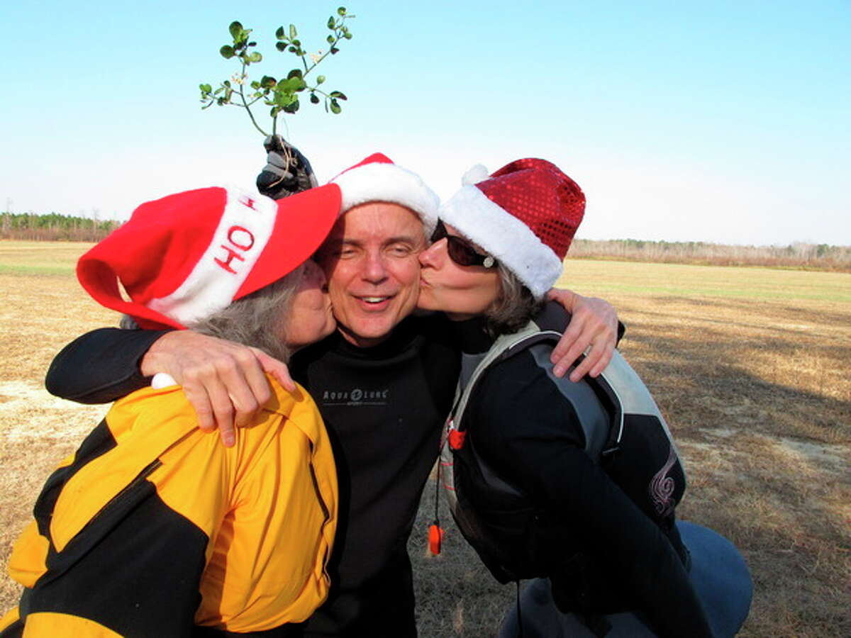 Nate Jackson of Chapel Hill, N.C., gets a smooch under the mistletoe from Camille Warren, left, and his neighbor Joan Monnig along the bank of the Upper Little River near Lillington, N.C., on Saturday, Dec. 1, 2012. They were part of the 30th annual Sprig Outing. (AP Photo/Allen Breed)