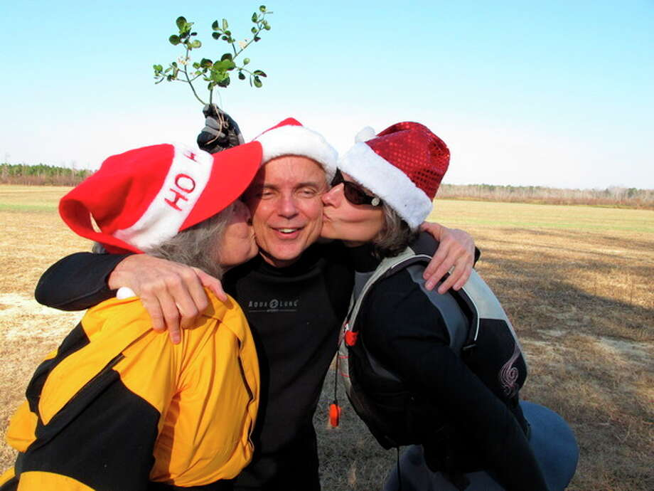 Nate Jackson of Chapel Hill, N.C., gets a smooch under the mistletoe from Camille Warren, left, and his neighbor Joan Monnig along the bank of the Upper Little River near Lillington, N.C., on Saturday, Dec. 1, 2012. They were part of the 30th annual Sprig Outing. (AP Photo/Allen Breed) / AP