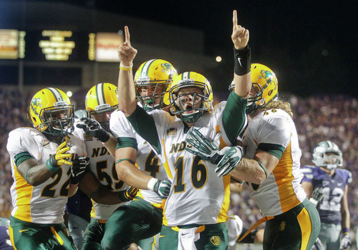 North Dakota State's quarterback Brock Jensen lets out a scream as his teammates rejoice with him after scoring with 28 seconds left in the fourth quarter, putting the Bison ahead 23-21, during an NCAA college football game in Manhattan, Kan., Friday, Aug. 30, 2013. North Dakota State upset Kansas State 24-21. (AP Photo/The Topeka Capital Journal, Chris Neal)