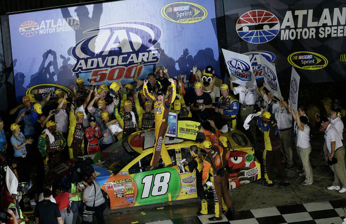 Sprint Cup Series driver Kyle Busch (18) celebrates in victory lane following the NASCAR Sprint Cup Series auto race at Atlanta Motor Speedway in Hampton, Ga., Sunday, Sept. 1, 2013. (AP Photo/John Bazemore)