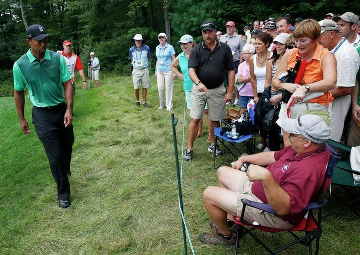 Tiger Woods, left, approaches Bernie Dresser,front right, of Newport, N.H., as Dresser points to the ball after it landed on his seat on the fifth green during the third round of the Deutsche Bank Championship golf tournament in Norton, Mass., Sunday, Sept. 1, 2013. (AP Photo/Michael Dwyer)