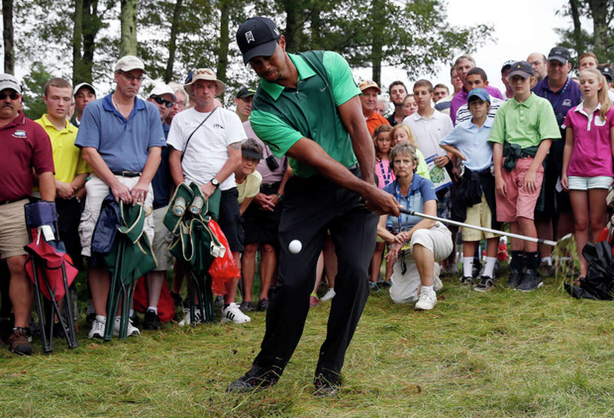 Tiger Woods chips from the rough onto the fifth green during the third round of the Deutsche Bank Championship golf tournament in Norton, Mass., Sunday, Sept. 1, 2013. (AP Photo/Michael Dwyer)