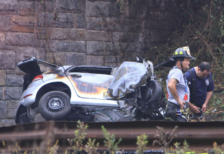 Police and firefighters work at the scene of a multi-fatal accident on the northbound Sprain Brook Parkway in Greenbugh, N.Y. on Sunday, Sept. 1, 2013. Police said the car hit the Underhill Road Bridge and burst into flames killing all four occupants early Sunday morning. (AP Photo/The Journal News, Frank Becerra Jr.)