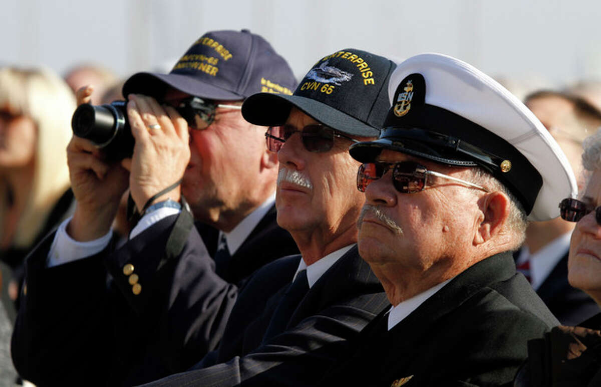 Retired crewmen from the USS Enterprise, Senior Chief, Fred Bridges, of Oskaloosa, Ia., right, Dennis Sult, of Ankney Ia., center, and seaman, Wayne Altstadt, of Evansville In., left listed to speakers during the inactivation ceremony for the first nuclear powered aircraft carrier USS Enterprise at Naval Station Norfolk Saturday, Dec. 1, 2012 in Norfolk, Va. The ship served in the fleet for 51 years. (AP Photo/Steve Helber)
