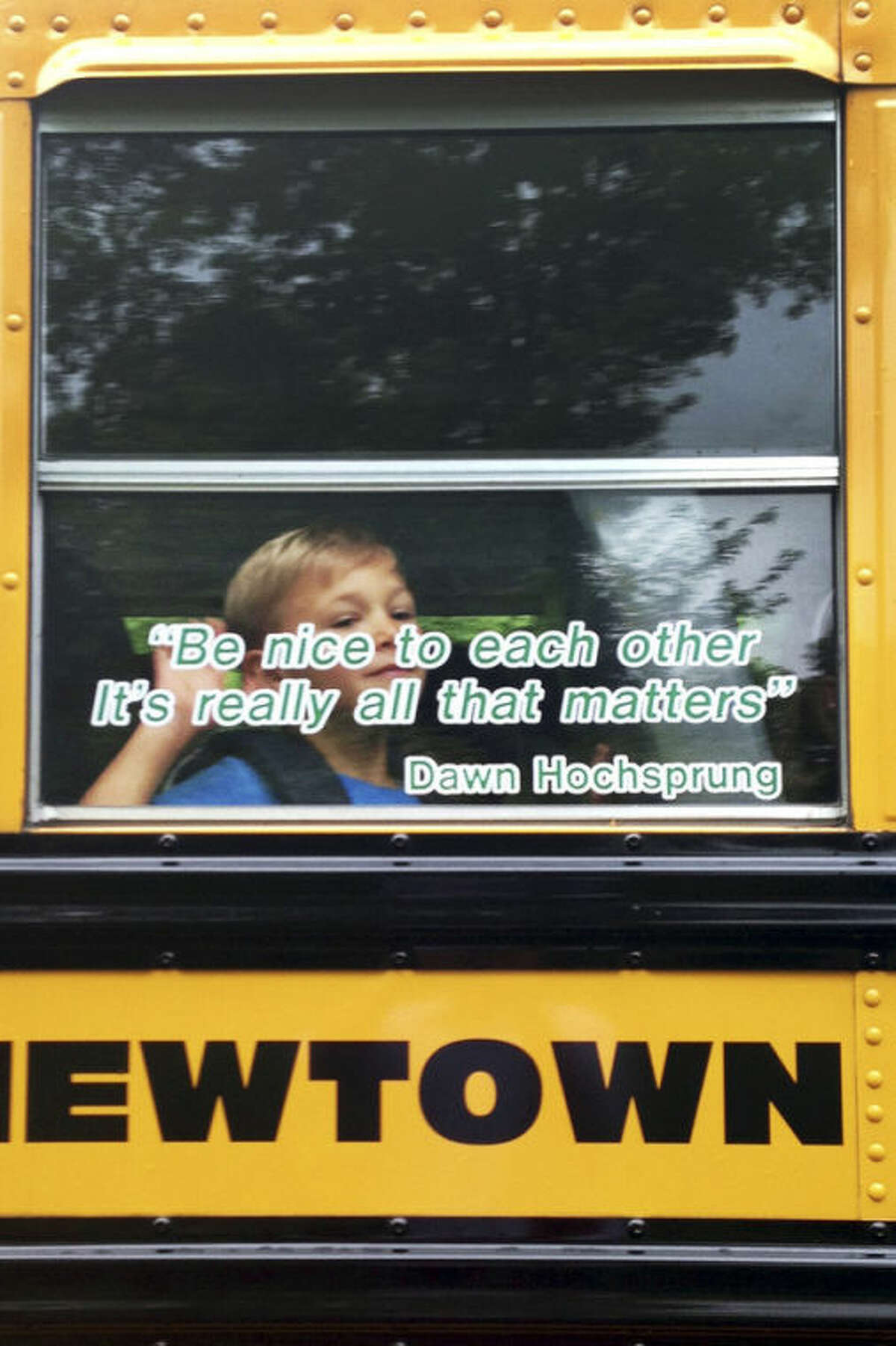 In this photo provided by Craig Hoekenga, his son Trey Hoekenga, a kindergarten student at Sandy Hook Elementary School, waves from the school bus on the first day of school Tuesday, Aug. 27, 2013, in Newtown, Conn. On the bus window is a quote by the late principal, Dawn Hochsprung: