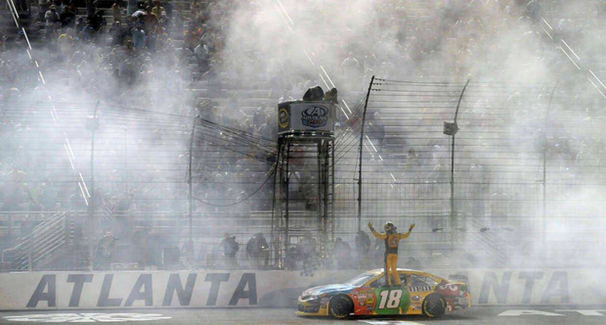 Sprint Cup Series driver Kyle Busch (18) celebrates after winning the NASCAR Sprint Cup Series auto race at Atlanta Motor Speedway in Hampton, Ga., Sunday, Sept. 1, 2013. (AP Photo/David Tullis)