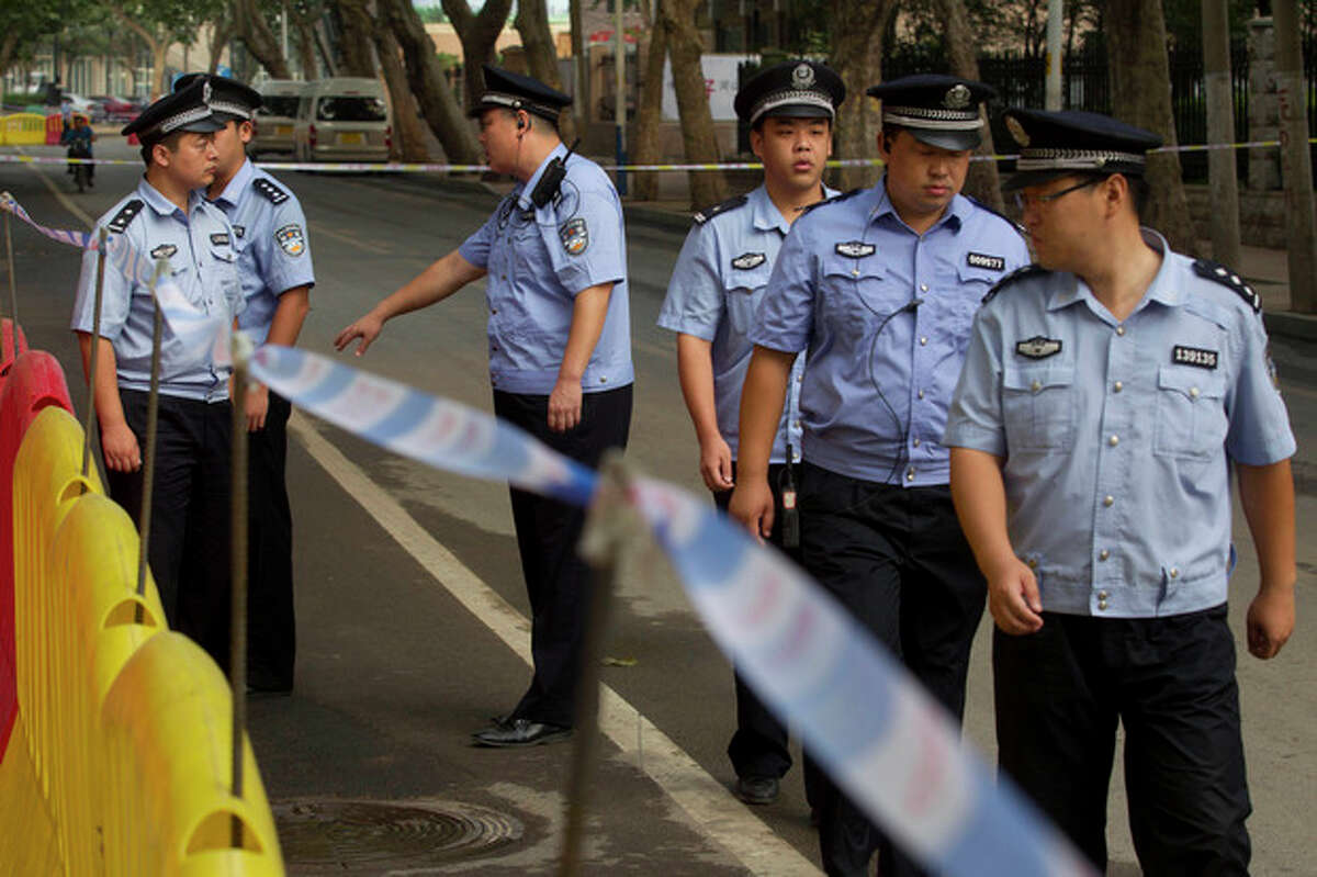 Chinese police officers on duty walk outside the Jinan Intermediate People's Court in Jinan in eastern China's Shandong province on Sunday, Aug. 25, 2013. Former Chinese politician Bo Xilai's trial on charges of bribery, embezzlement and abuse of power goes on for a fourth day. (AP Photo/Ng Han Guan)