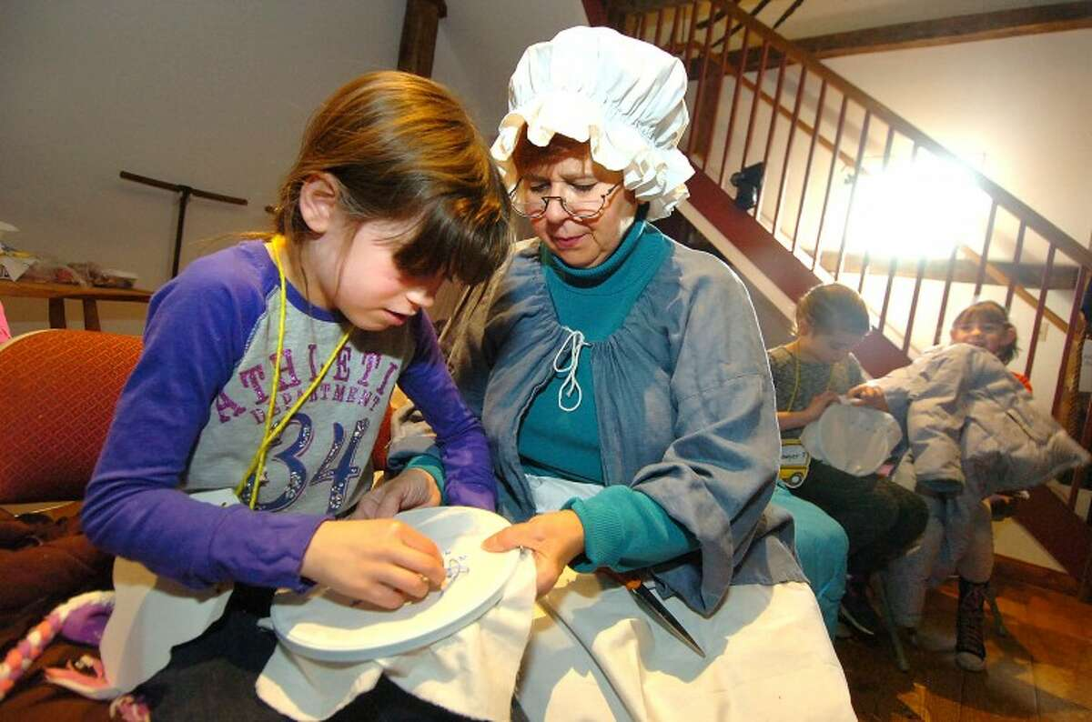 Hour Photo/Alex von Kleydorff. 2nd Grader Emma Oliveri gets a taste of colonial life with help on her Cross Stich from Bunny Sicard at The Wilton Historical Society