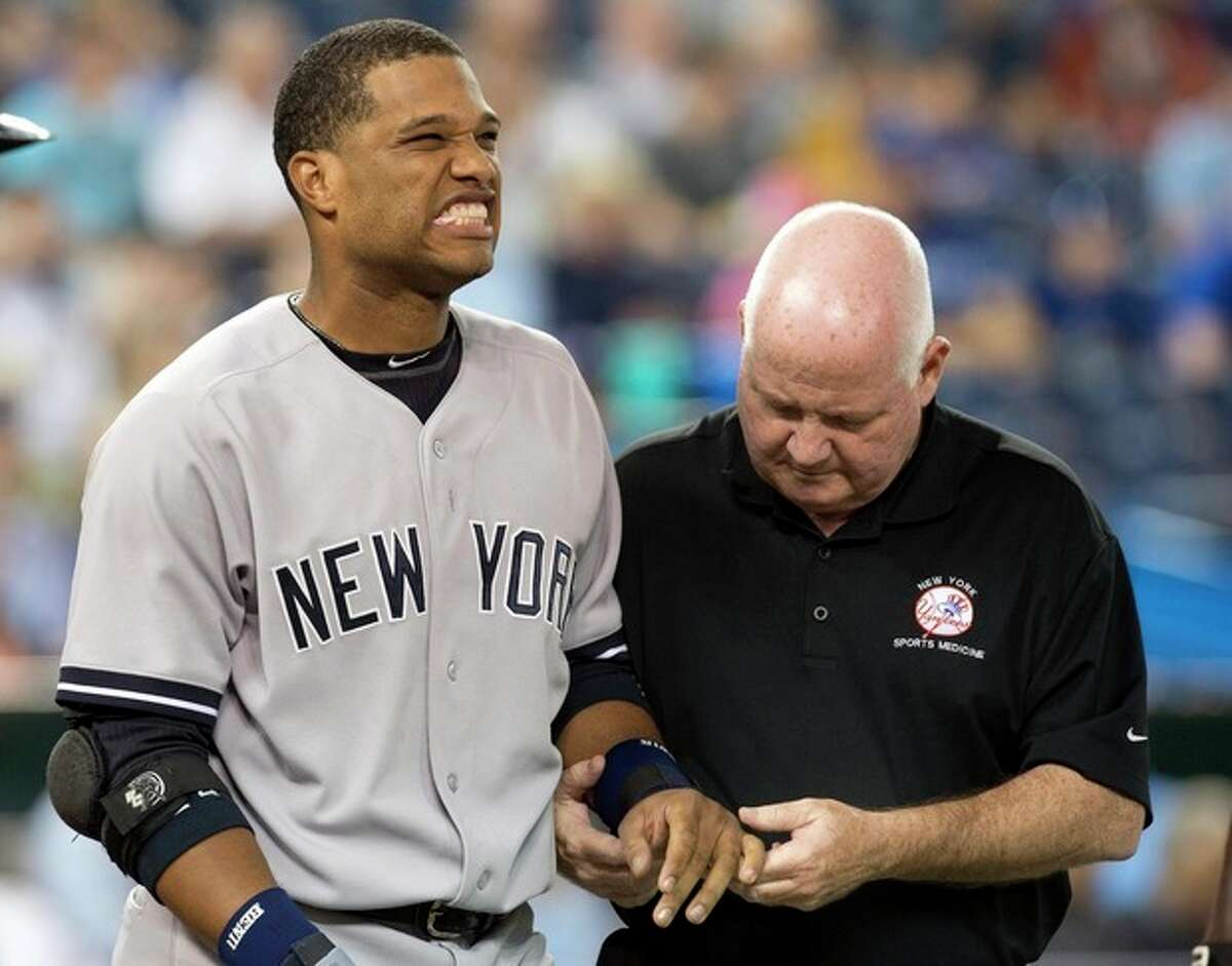 New York Yankees' Robinson Cano is attended to by trainer Steve Donohue after getting hit on the hand by a pitch from Toronto Blue Jays starting pitcher J.A. Happ during the first inning of a baseball in Toronto on Tuesday, Aug. 27, 2013. (AP Photo/The Canadian Press, Frank Gunn)