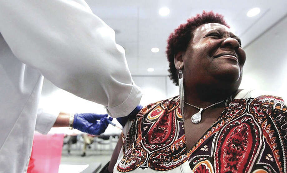 FILE - In a Tuesday, Oct. 30, 2012 file photo, Elizabeth Saint Victor winces as she gets a free flu shot from LPN Jean Buck courtesy of Baptist Healthcare in Memphis, Tenn., at the Central Library. Health officials say flu season is off to its earliest start in nearly 10 years _ and it could be a bad one. Officials said Monday, Dec. 3, 2012 that suspected flu cases have jumped in five southern states _ Alabama, Louisiana, Mississippi, Tennessee and Texas. An uptick in flu reports like this usually doesn't occur until after Christmas. (AP Photo/The Commercial Appeal, Jim Weber, File) / The Commercial Appeal