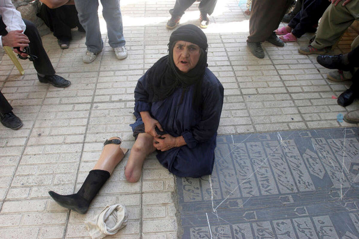 FILE - In this Tuesday, June 26, 2007 file photo, Iranian Sanjan Salimzadegan, who lost her right leg during the 1980-88 Iran-Iraq war, shows her artificial leg, as she weeps at the grave of her children who were killed during a chemical attack in July 22 of 1988 at the Zardeh village, Iran. For more than a generation, Iranian newspapers regularly post notices: Another veteran of the 1980s' war with Iraq has died of complications from exposure to chemical weapons from Saddam Hussein's arsenal. The claims now that Iran's Syrian allies used similar battlefield tactics, including possibly unleashing sarin gas, forced Tehran's leaders into perhaps their most difficult juncture of the nearly 30-month Syrian civil war: How much to stick by Bashar Assad if the Western allegations are backed by U.N. inspection teams. (AP Photo/Vahid Salemi, File)