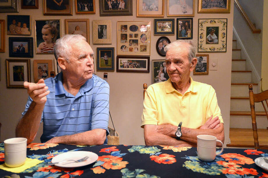 Hour Photo/Alex von Kleydorff. Brothers Alan and Lee Seymour talk with family over coffee and cookies with a backdrop of a wall covered with family photos at the home of Rebecca and Bill Sweeney in Norwalk