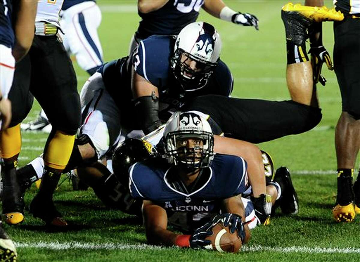 Connecticut running back Lyle McCombs, bottom, looks up to an official at the goal line during the first half of an NCAA college football game against Towson at Rentschler Field in East Hartford, Conn., Thursday, Aug. 29, 2013. McCombs ran for a gain of 22 yards to the 1 yard line. Connecticut failed to score a touchdown on the drive. (AP Photo/Jessica Hill)