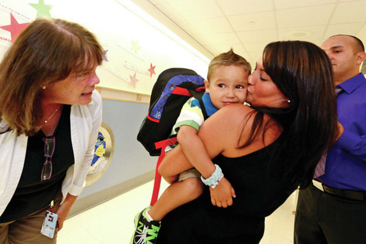 Hour photo / Erik Trautmann Teacher Abby Peterson greets Peyton Roman and his parents Shannon and Andre during Peyton's first day of preschool at Brookside Elementary.