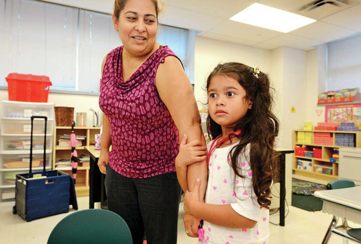 Hour photo / Erik Trautmann Melanie Vaquiz holds on to her mother, Marta Vaquiz, during the first day of kindergarten at Brookside Elementary on Thursday.