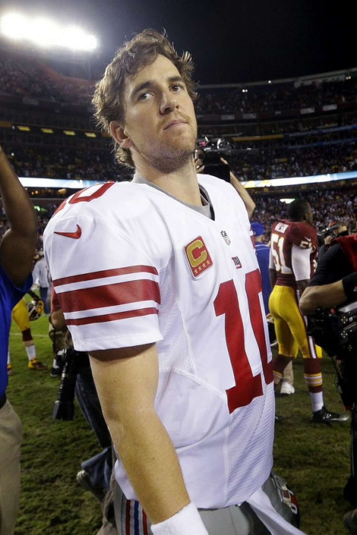 New York Giants quarterback Eli Manning looks over his shoulder as he leaves the field after an NFL football game against the Washington Redskins in Landover, Md., Monday, Dec. 3, 2012. The Redskins won 17-16. (AP Photo/Patrick Semansky)