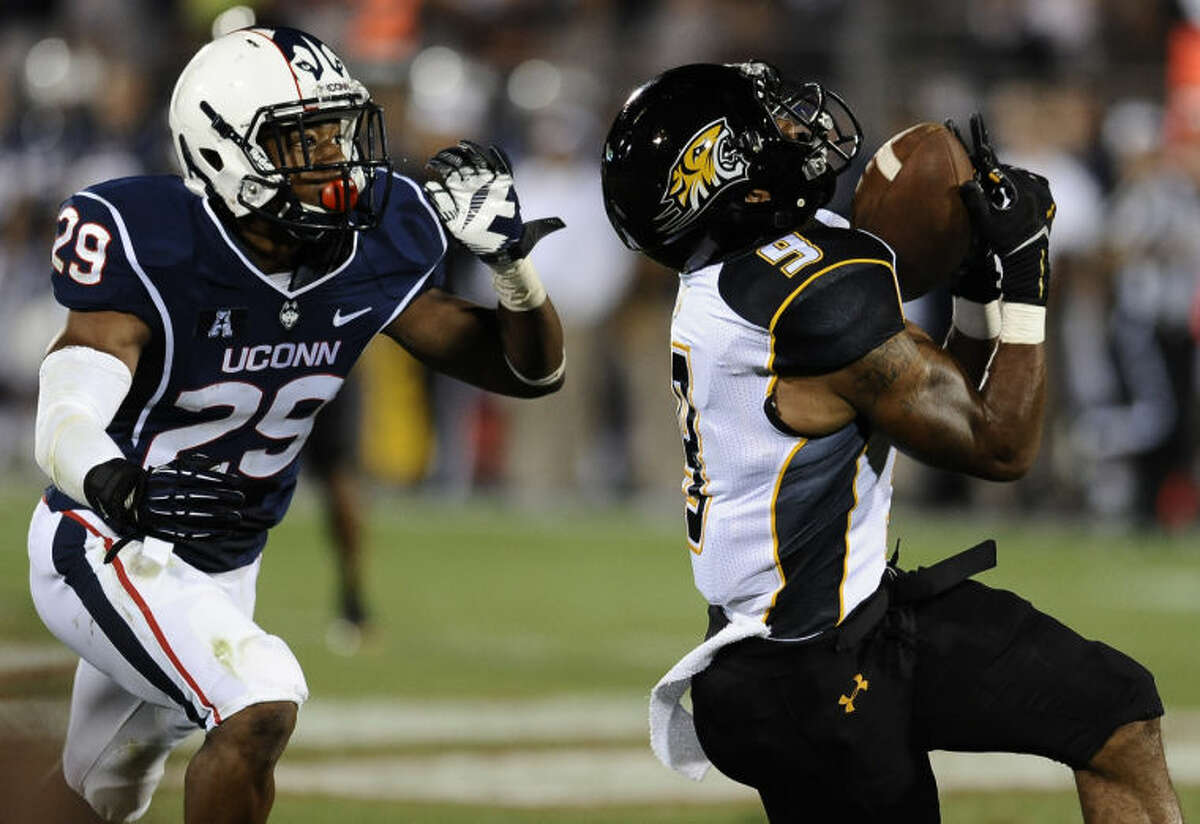 Towson wide receiver Leon Kinnard (9) catches the ball as Connecticut cornerback Taylor Mack (29), left, defends during the second half of an NCAA college football game at Rentschler Field in East Hartford, Conn., Thursday, Aug. 29, 2013. (AP Photo/Jessica Hill)