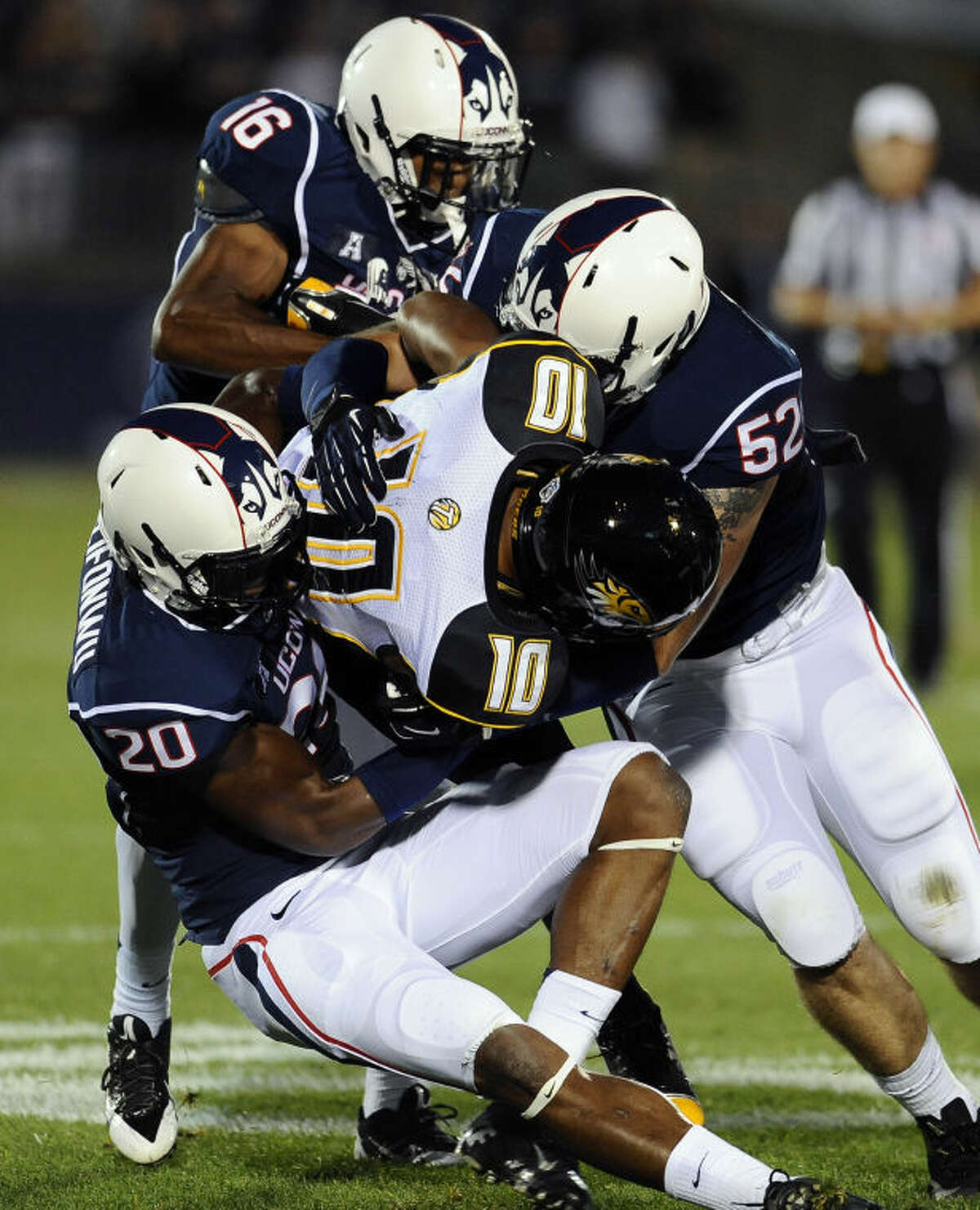 Towson wide receiver Spencer Wilkins (10), is pulled down by Connecticut safety Obi Melifonwu (20), Connecticut cornerback Byron Jones (16), and Connecticut linebacker Ryan Donohue (52), during the first half of an NCAA college football game at Rentschler Field in East Hartford, Conn., Thursday, Aug. 29, 2013. (AP Photo/Jessica Hill)
