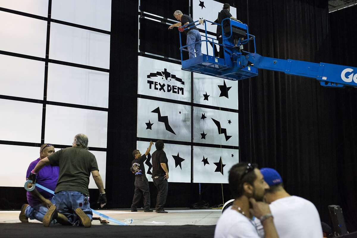 Workers set the stage, lifting lights and laying carpet, for the Texas Democratic Convention, which will be held at the end of this week, at the Alamodome in San Antonio on Wednesday, June 15, 2016.