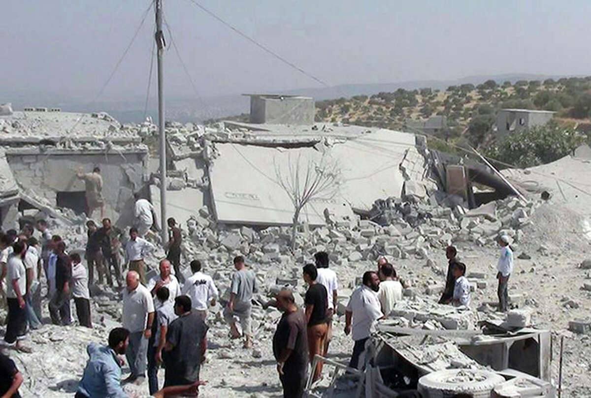 In this citizen journalism image provided by Edlib News Network, ENN, which has been authenticated based on its contents and other AP reporting, Syrians search under rubble to rescue people from houses that were destroyed by a Syrian government warplane, in Idlib province, northern Syria, Friday, Aug. 30, 2013. United Nations experts are investigating the alleged use of chemical weapons in Syria as the United States and its allies prepare for the possibility of a punitive strike against President Bashar Assad's regime, blamed by the Syrian opposition for the attack. The international aid group Doctors Without Borders says at least 355 people were killed in the Aug. 21 attack in a suburb of Damascus, the Syrian capital. (AP Photo/Edlib News Network ENN)